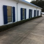 Aluminum Board & Batten Shutters powder coat painted blue were installed on a Houma Insurance Agency building to replace their rotting wood shutters.