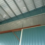 Aluminum Storm Panels custom cut to fit across a large crane opening on a commercial building.
