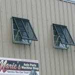 Aluminum Bahama Shutters installed on a second floor window on a Houma commercial building.